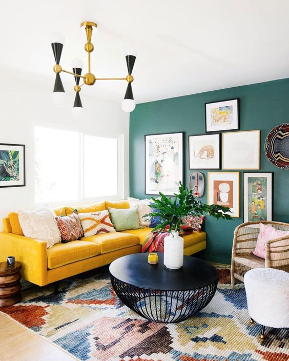 a bright living room with a green wall, a bright yellow sofa, a colorful printed rug, a bright gallery wall and a mid-century modern chandelier