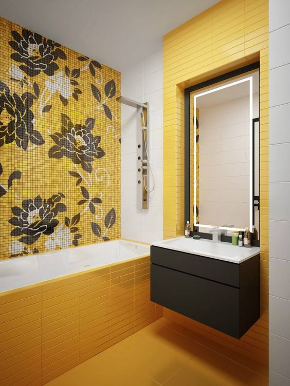 a bright modern bathroom with yellow tiles, a floral tile wall and a grey vanity plus lights for an accent