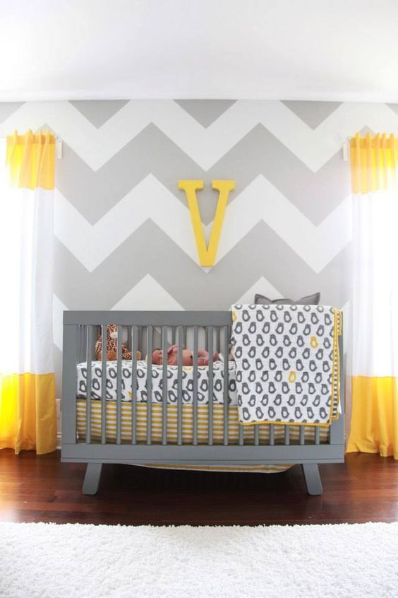 a bright nursery with grye and white chevron walls, color block curtains, a grey crib and printed bedding plus a monogram on the wall
