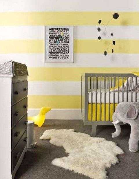 a bright nursery with striped yellow and white walls, grey furniture, a faux fur rug, a mobile and a toy elephant