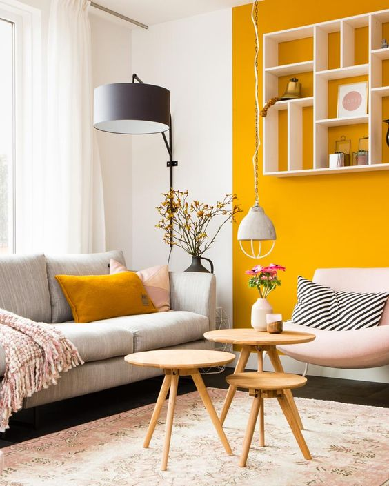 a chic contemporary living room with a marigold accent wall and a pillow, neutral and pastel furniture, a floor lamp and mini wooden tables