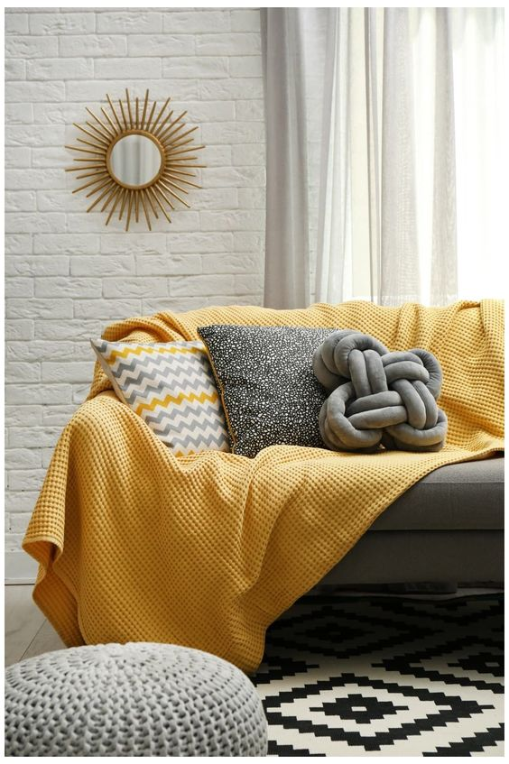 a chic living room with faux white brick walls, a grey sofa, grey and yellow pillows, a grey ottoman and a yellow blanket