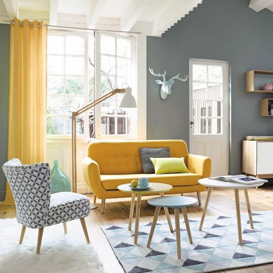 a chic living room with grey walls, a yellow sofa and a printed chair, yellow curtains and round coffee tables
