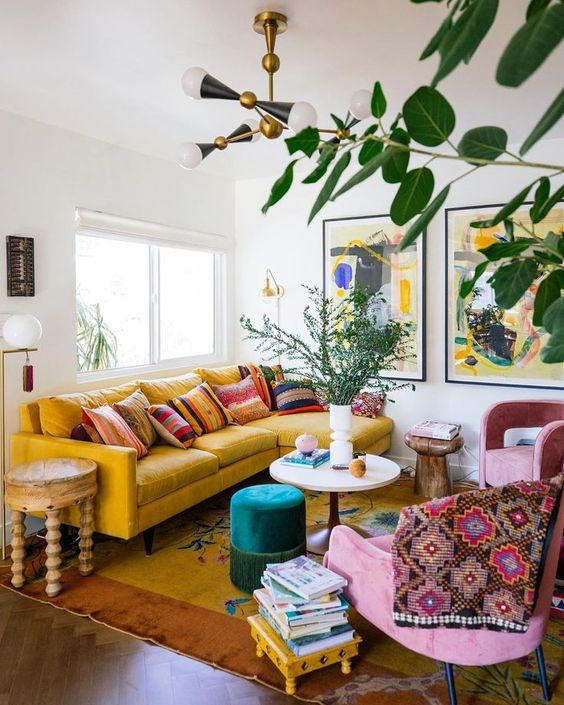 a colorful boho living room with a yellow sofa and a rug, pink chairs, bold printed textiles, a green ottoman, wooden stools and tables