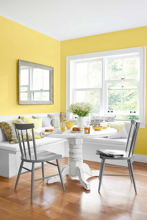 a colorful dining nook with yellow walls, a white corner seat, a white table, grey chairs and grey and yellow pillows