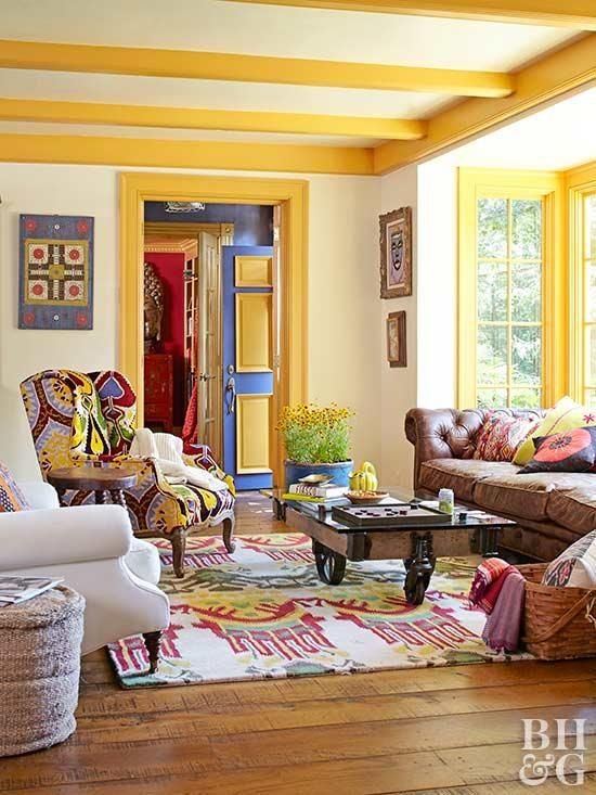 a colorful living room with yellow beams and frames, a brown leather sofa, colorful chairs and a rug, a coffee table on casters