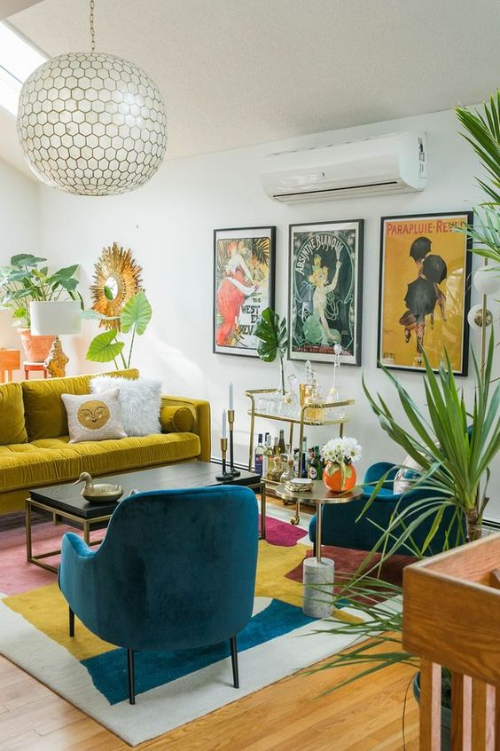 a colorful mid-century modern living room with a mustard sofa, a bold rug, teal chairs, a bright gallery wall and potted plants