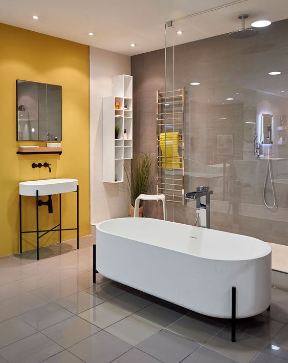 a contemporary bathroom with a grey wall and a yellow one, white appliances, a shower space and a couple of racks for storage