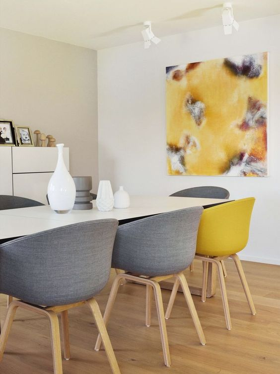 a contemporary dining room with neutral walls, a storage unit, a white table, grey and yellow chairs and a matching artwork