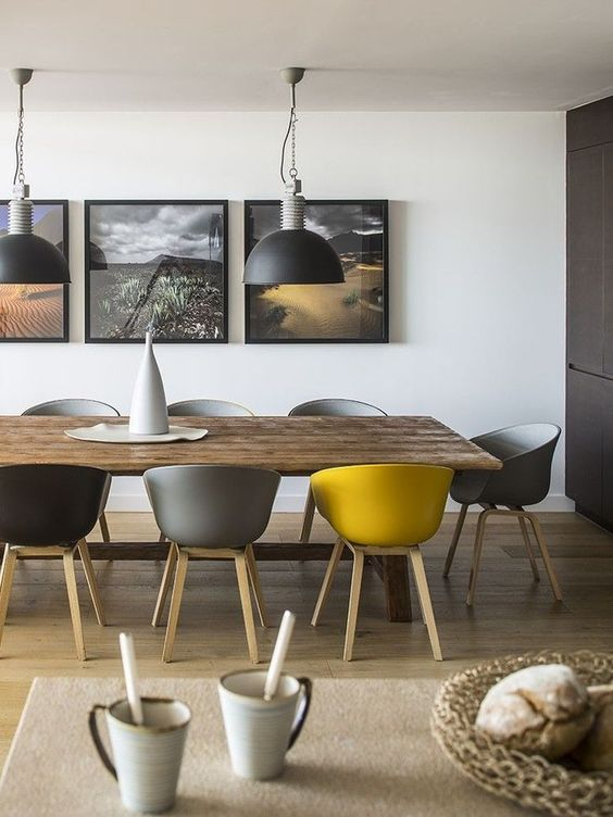 a contemporary grey and yellow dining room, with a wooden table, grey, black and yellow chairs, pendant lamps and a matching gallery wall