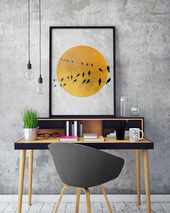 a contemporary home office with grey concrete walls, a pretty black and yellow desk, a grey chair, pendant lamps and a bold print
