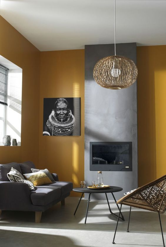 a contemporary living room with mustard walls, a fireplace built into a concrete panel, a grey sofa, a rattan chair and a rattan pendant lamp