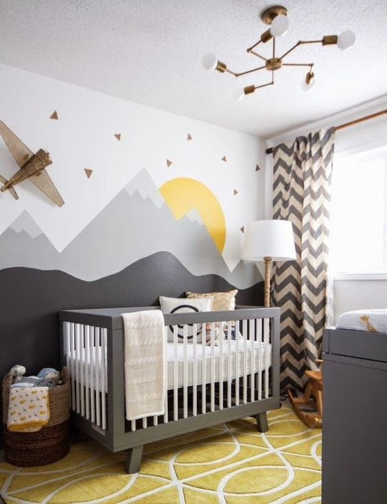 a cool mountain nursery with a moutain accent wall, grey furniture, a mustard rug, chevron curtains is veyr adventurous