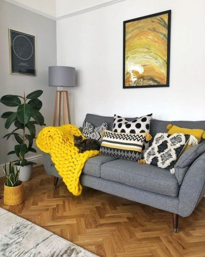 a cozy living room with a grey sofa, a grey floor lamp, a lemon yellow blanket and pillows plus a bold artwork