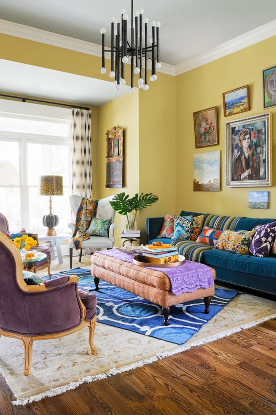 a crazily colorful living room with yellow walls, a navy sofa, a pink ottoman and a purple chair, colorful rugs, pillows and upholstery