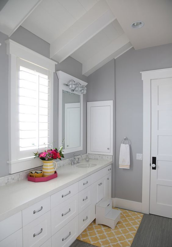 a farmhouse bathroom with grey walls, white furniture and appliances, silver fixtures, bold yellow accents and bright blooms