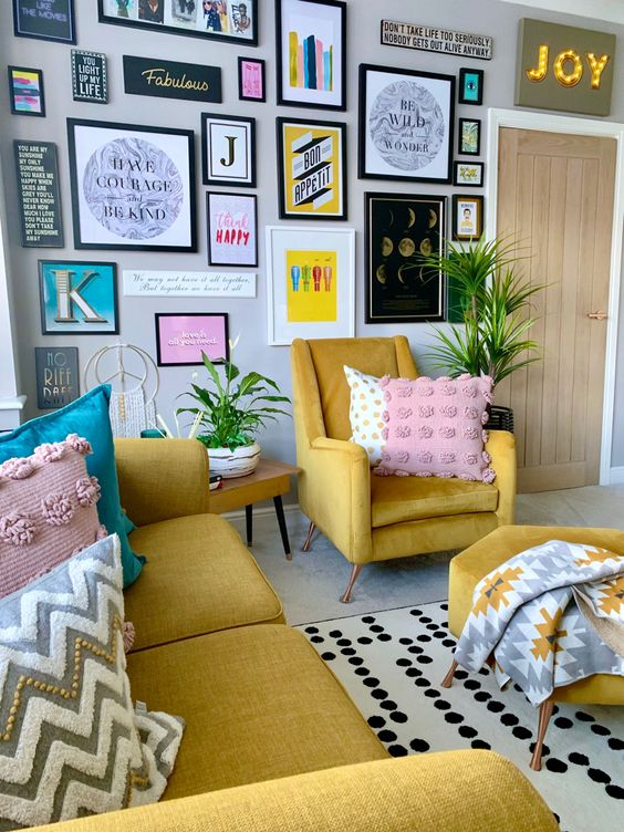 a fun and bright living room with a yellow sofa and chairs, printed pillows and blankets, a bold gallery wall and a marquee light