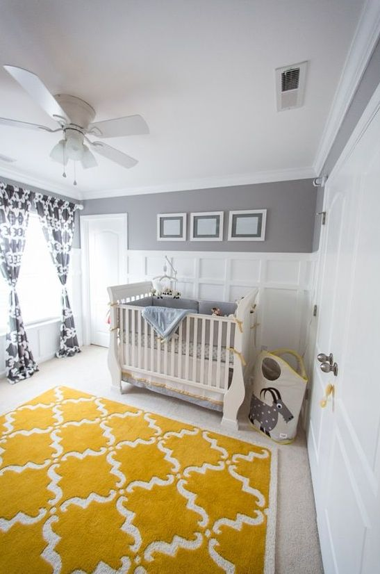 a fun and whimsical nursery with grey and white paneled walls, neutral furniture, grey bedding, a mustard rug and printed curtains