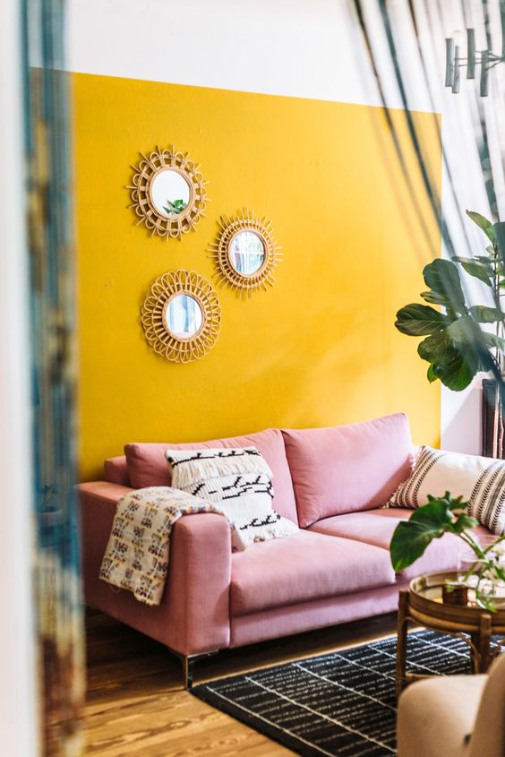 a fun living room with a yellow accent wall, a pink sofa, printed textiles, sunburst mirrors and potted plants