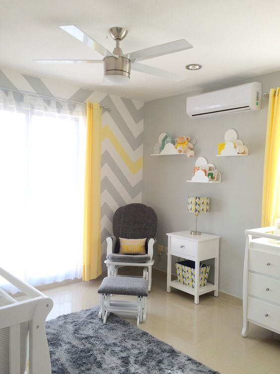 a grey nursery with a chevron, white furniture, a grey chair with a stool and cloud-shaped shelves for books