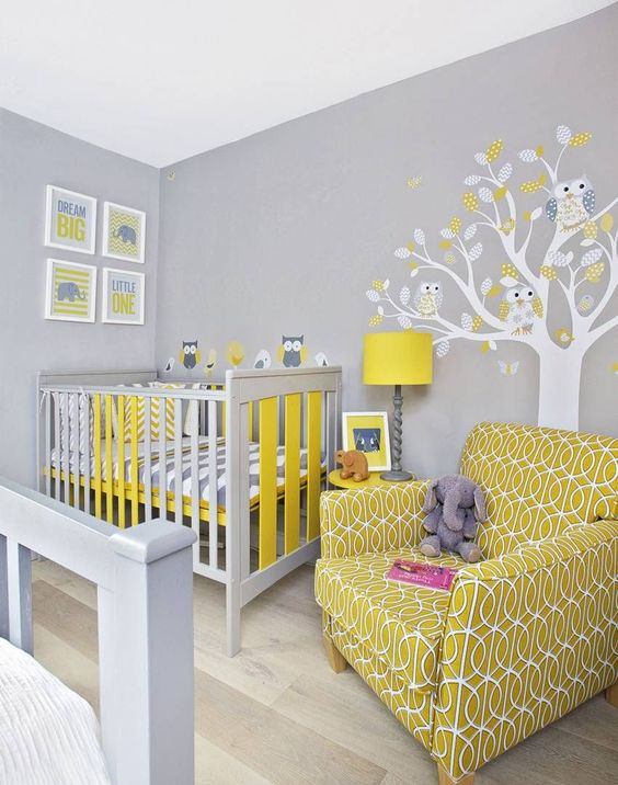 a grey nursery with a tree with owls, a grey and yellow crib, a mustard printed chair and a pretty gallery wall