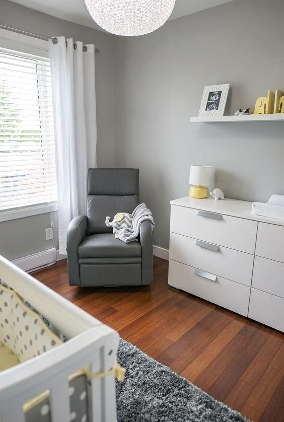 a grey nursery with white furniture, a grey chair, some white, grey and yellow textiles and an open shelf with artworks