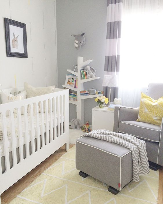 a grey, white and yellow nursery with grey walls, color block curtains, a grey chair and an ottoman, a white crib and yellow touches