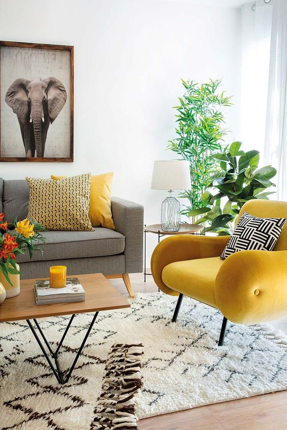 a mid-century modern living room with a grey sofa, a lemon yellow chair, printed pillows, potted plants and a bold artwork