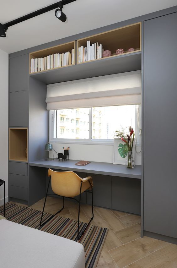 a minimalist home office nook with a built in storage unit, a window for a view, a small yellow chair is all you need for work