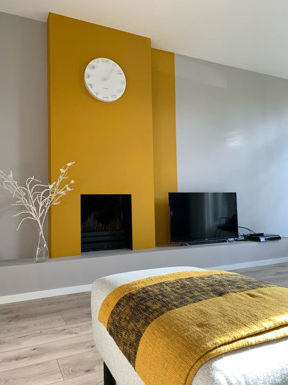 a minimalist living room with dove grey walls, mustard panels over the fireplace, a clock and a daybed with a yellow blanket