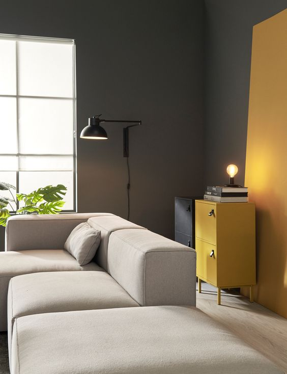 a minimalist living room with grey walls, honey yellow touches, a black and a honey yellow cabinet, a creamy sectional and a black lamp