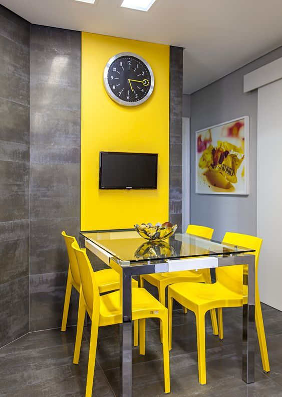 a modern colorful dining room with a glass dining table, yellow chairs, a grey wall with a color block effect done with a yellow panel