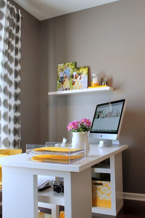 a modern home office with grey walls, a white desk with yellow touches and a yellow chair, printed grey curtains is simple and cool