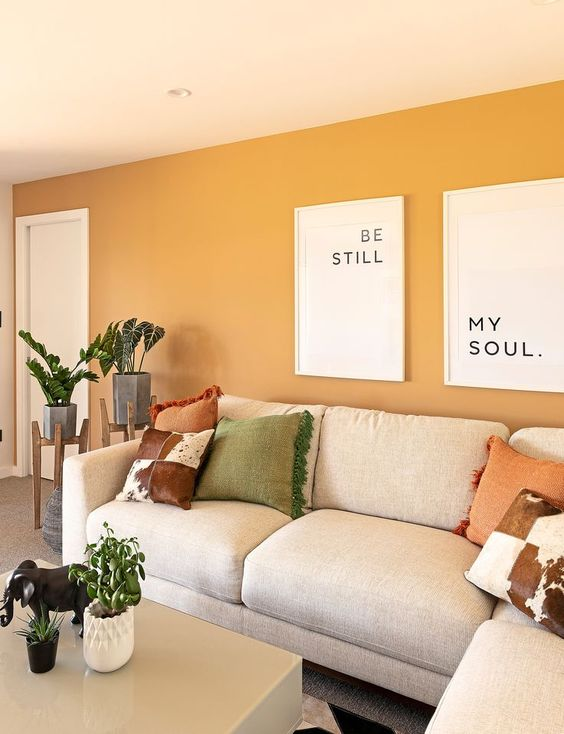 a modern living room with yellow walls, neutral furniture, printed pillows, potted greenery and some cool prints