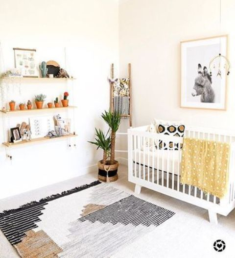 a neutral boho nursery with neutral furniture, a boho rug, a suspended shelf, mustard bedding and a wall art