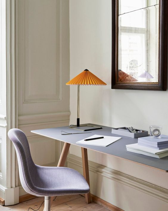 a neutral sophisticated home office with a grey trestle desk, a grey chair and a yellow lamp with a pleated shade