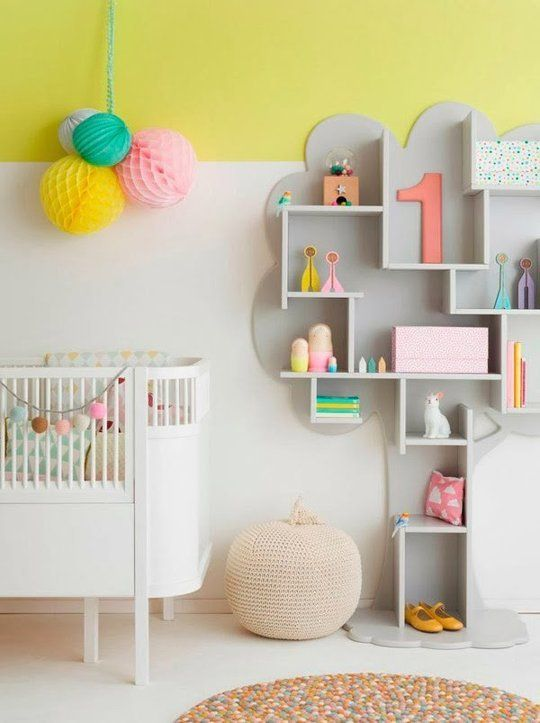 a nursery with color block white and yellow walls, a whisical grey shelf, a white crib and some bold paper pompoms