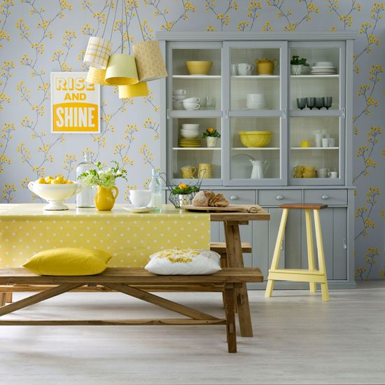 a pretty and cute grey and yellow dining room with floral wallpaper, a grey buffet, a wooden dining set, pendant lamps and yellow textiles