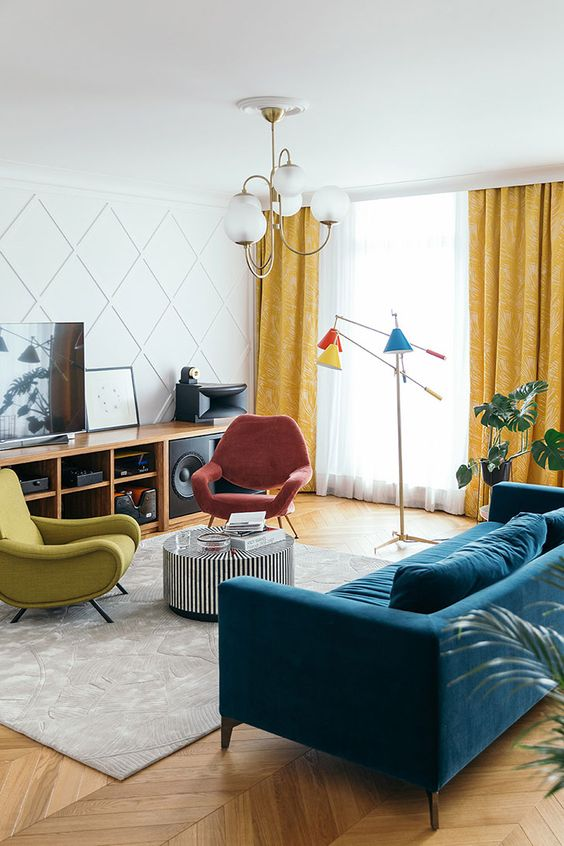 a pretty mid-century modern living room with a navy sofa, red and lemon chairs, yellow curtains, colorful lamps