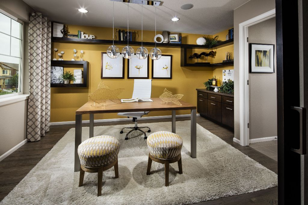 a quirky home office with a honey yellow accent wall and lots of dark open shelves, a gallery wall, a desk, printed grey and yellow ottomans and yellow wire fish