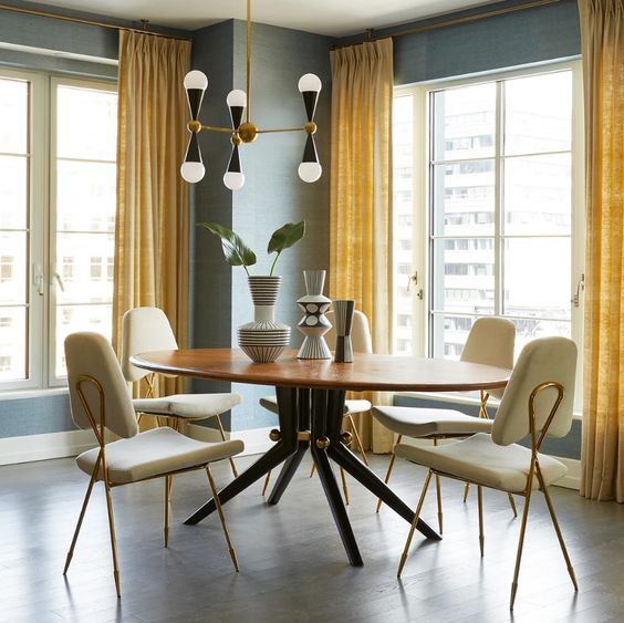 a refined and elegant grey and yellow dining room with grey walls, yellow curtains, a round dining table, neutral chairs and a pretty chandelier