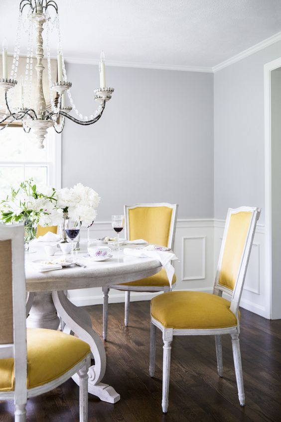 a refined classic dining room with grey walls, paneling, a large white table, yellow chairs, a beautiful crystal chandelier and white blooms