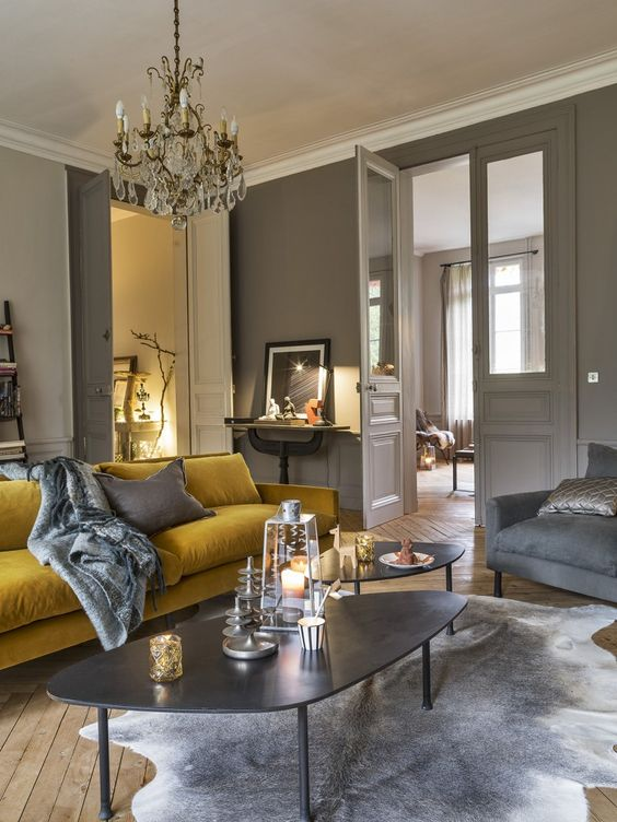 a refined dove grey living room with a mustard sofa, grey chairs, cool coffee tables and a crystal chandelier plus artworks