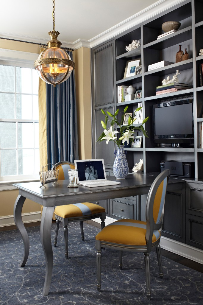 a refined home office with yellow walls, a large built in grey storage unit, a grey desk and grey and yellow chairs, grey curtains and a chic pendant lamp