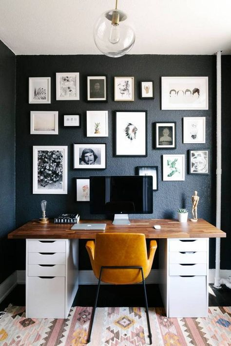 a refined mid century modern home office with a graphite grey wall with a black and white gallery wall, a desk, a yellow leather chair