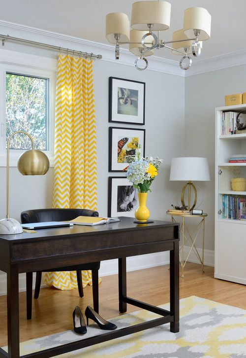 a refined mid century modern home office with light grey walls, a dark desk and a dark chair, a brass lamp and a grey and yellow printed rug