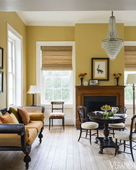 a refined vintage living room with pale yellow walls, a fireplace, dark wooden furniture with yellow upholstery and a crystal chandelier