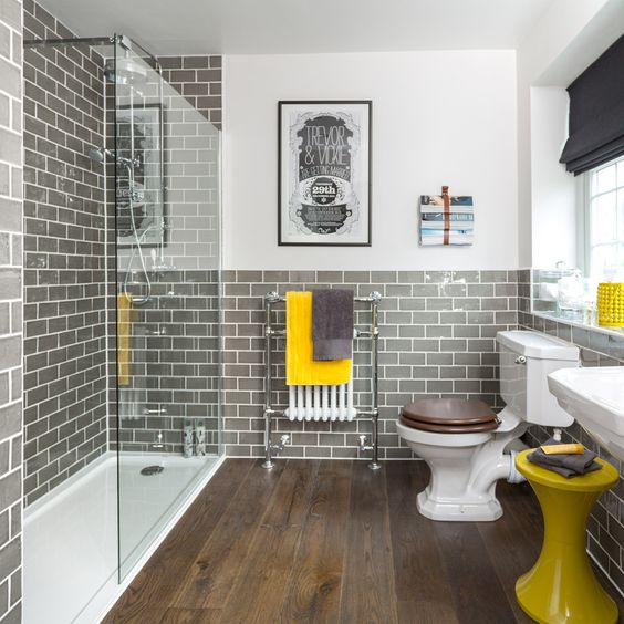 a retro bathroom with white walls and grey subway tiles, with white appliances, yellow touches and black shades