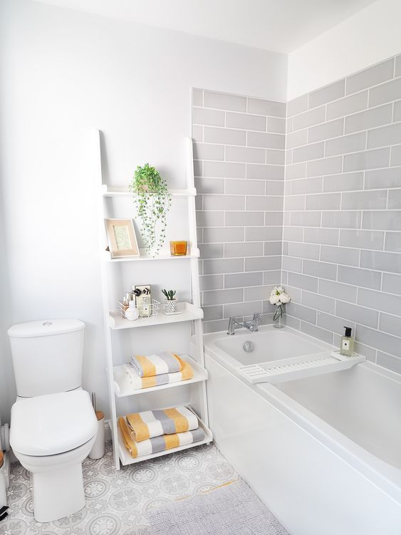 a serene bathroom with grey subway tiles, white appliances and a shelf, grey, white and yellow towels