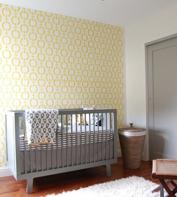 a simple and cute nursery with a yellow accent wall, a grey crib, printed bedding and woven touches
